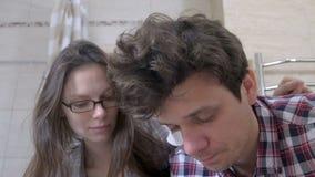 Slaperige paarman en vrouw in de badkamers die met kater in orde proberen te zetten stock footage