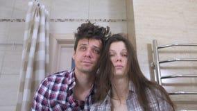 Slaperige paarman en vrouw in de badkamers die met kater proberen te ontwaken stock videobeelden