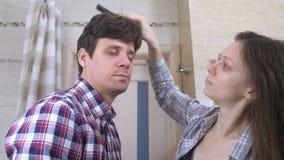 Slaperige paarman en vrouw in de badkamers De vrouw kamt man haar en zij koesteren elkaar stock videobeelden