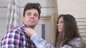 Slaperige paarman en vrouw met kater in de badkamers De vrouw kamt man haar en het proberen te ontwaken stock videobeelden