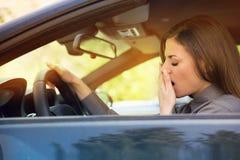Slaperige vermoeide geeuwende jonge vrouw die haar auto drijven stock afbeelding