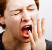 Slaperige vermoeide vrouw die een grote geeuw maakt Stock Foto