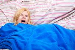 Slaperige vrouwengeeuw in een dekbed Royalty-vrije Stock Fotografie