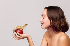 Slapp fokus isolering inom Barn och hållande äpple för brunettflicka som sitter på en gecko fotografering för bildbyråer