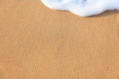 Slapp wave av havet på den sandiga stranden Royaltyfria Foton