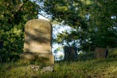 Slappt tänd allvarlig markör på en gammal kyrkogård arkivbild