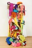 Slarvig belamrad kvinnagarderob med kläder och tillbehör som faller ut ur en hylla arkivfoton