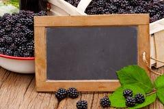 Slate blackboard in front of ripe blackberries Royalty Free Stock Image
