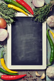 Slate board with fresh vegetables. Spice and herbs on wooden background. Top view Stock Images