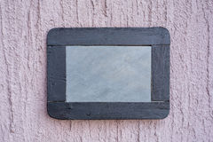 Slate board on rough wall Stock Images