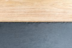 Slate board on wooden background. Black and gray slate textured flat stone laying on brown wooden desk table background Stock Photography