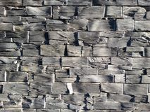 Slate brick wall. Close up view of a homogeneous grey brick made of slate bricks with an intense shadow play stock photography