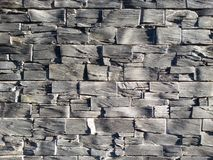Slate brick wall. Close up view of a homogeneous grey brick made of slate bricks with an intense shadow play stock image