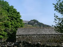 Slate building by trees with mountain behind Stock Images