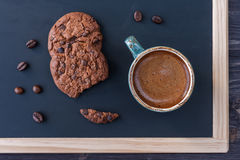 Slate chalk board with a cup of coffee and chocolate chip cookies Stock Photo