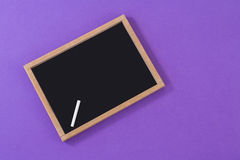 Slate with chalk. On purple background Stock Photography