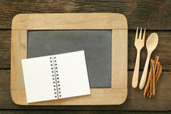 Slate chalkboard and wooden spoon and blank earth tone note book with cinnamon Stock Image