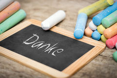 Slate and colorful chalk on wooden table Stock Photo