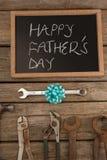 Slate con las herramientas felices del texto y de la mano del día de padres en la tabla Imagen de archivo libre de regalías