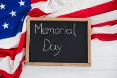 Slate con testo e una bandiera americana sulla tavola di legno Fotografia Stock