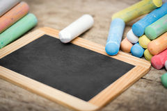 Slate with copyspace and colorful crayon on wooden table Royalty Free Stock Photos