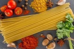 Slate cutting Board. Composition spaghetti spices for cooking Italian dishes. Royalty Free Stock Photo