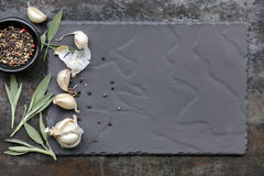 Slate Food Background with Garlic Cloves Sage Leaves and Black P Stock Images