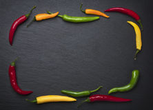 Slate framed by colorful chili peppers. Royalty Free Stock Photography