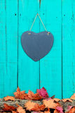 Slate heart hanging on fence with fall decor border. Slate heart hanging on rustic teal blue wood background by log covered in autumn leaves Royalty Free Stock Photos