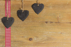 Heart of slate on a wood panel. Slate heart lies on a red border. Behind an old wooden board Royalty Free Stock Image
