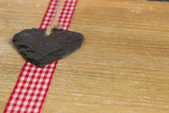 Heart of slate on a wood panel. Slate heart lies on a red border. Behind an old wooden board Stock Photography