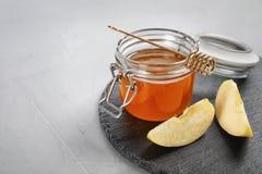 Slate la placa con el tarro de la miel, de manzanas cortadas y del cazo Fotos de archivo