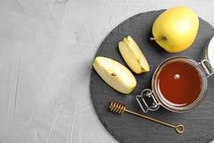 Slate la placa con el tarro de la miel, de manzanas y del cazo Fotografía de archivo libre de regalías