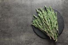 Slate le plat avec les brindilles fraîches de romarin sur le tabl photos stock
