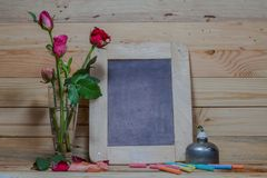 Slate, pastel and roses on the pinewood table Stock Image
