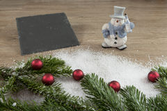 Slate, muñeco de nieve con las bolas rojas y verde del abeto Foto de archivo