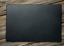 Slate over old wooden background Stock Images