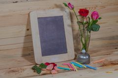 Slate, pastel and roses on the pinewood table Royalty Free Stock Photography