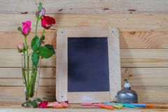 Slate, pastel and roses on the pinewood table. Slate leaning the wooden wall pastel and roses on the pinewood table Royalty Free Stock Photo