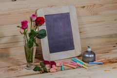 Slate, pastel and roses on the pinewood table Stock Photography
