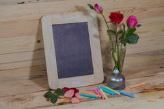 Slate, pastel and roses on the pinewood table. Slate leaning the wooden wall pastel and roses on the pinewood table Stock Images