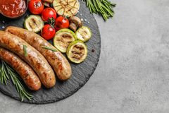 Slate plate with delicious barbecued sausages and vegetables on gray background. Space for text stock photos