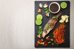 Slate plate with delicious fish, sauce and ingredients Royalty Free Stock Images