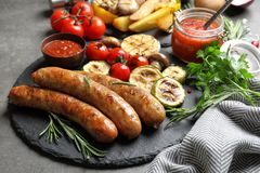 Slate plate with delicious sausages and vegetables served for barbecue party. On gray table royalty free stock photography