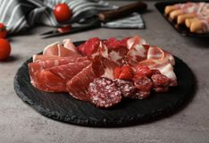 Slate plate with different meat delicacies. On gray table stock photos