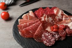Slate plate with different meat delicacies. On gray table stock photography