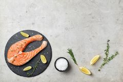 Slate plate with fresh raw salmon steak. On gray background, top view Royalty Free Stock Photo