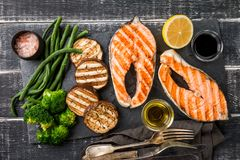 Grilled salmon steaks. Slate plate with grilled salmon steaks and vegetables on black wooden table, top view royalty free stock image