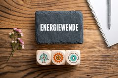 Slate plate with message `energy revolution ` in German and cubes with related icons royalty free stock images