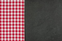 Slate plate with a red checkered tablecloth. Slate plate with a checkered tablecloth Royalty Free Stock Images